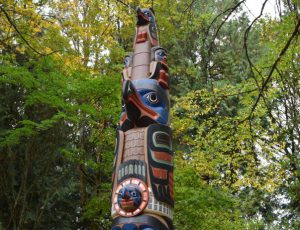 "The second file on the pole is the Eagle Princess. She is shown her in eagle form, looking out to sea, provided her protective spirit over her husband. On top of her are three ""look outs,"" whose job it is to warn the village of an approaching canoe."