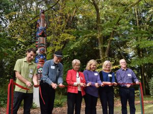 A ribbon-cutting ceremony for the pole was held on October 16, 2015. From left to right: Mike Schwindeller (Seattle Parks), Dale Faulstich (pole carver), Paige Miller (Arboretum Foundation), and the Faulstich family (Clairann, Julie, and Robert).