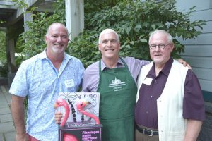 Jim Reid (center), with partner Richard Smith (left), and director emeritus of the Arboretum John Wott. Jim received a personalized green apron for his Volunteer Legacy Award and also a special gift from John for his garden.